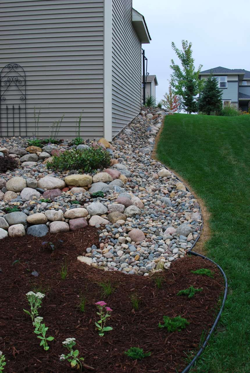Dry creek and raingarden used to redirect water around a home